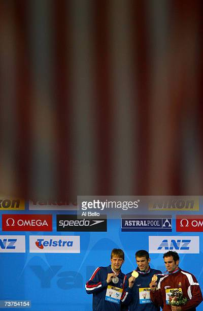 Silver medalist Ian Crocker of the United States of America gold medalist Michael Phelps of the United States of America and bronze medalist Albert...