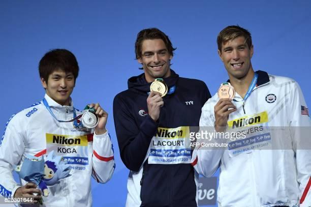 Silver medalist Japan's Junya Koga gold medalist France's Camille Lacourt and bronze medalist US Matt Grevers celebrate on the podium of the men's...