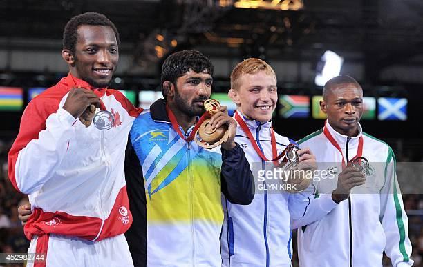 Silver medalist Jevon Balfour of Canada Gold medalist Yogeshwar Dutt of India and Bronze medalists Alex Gladkov of Scotland Sampson Clarkson of...