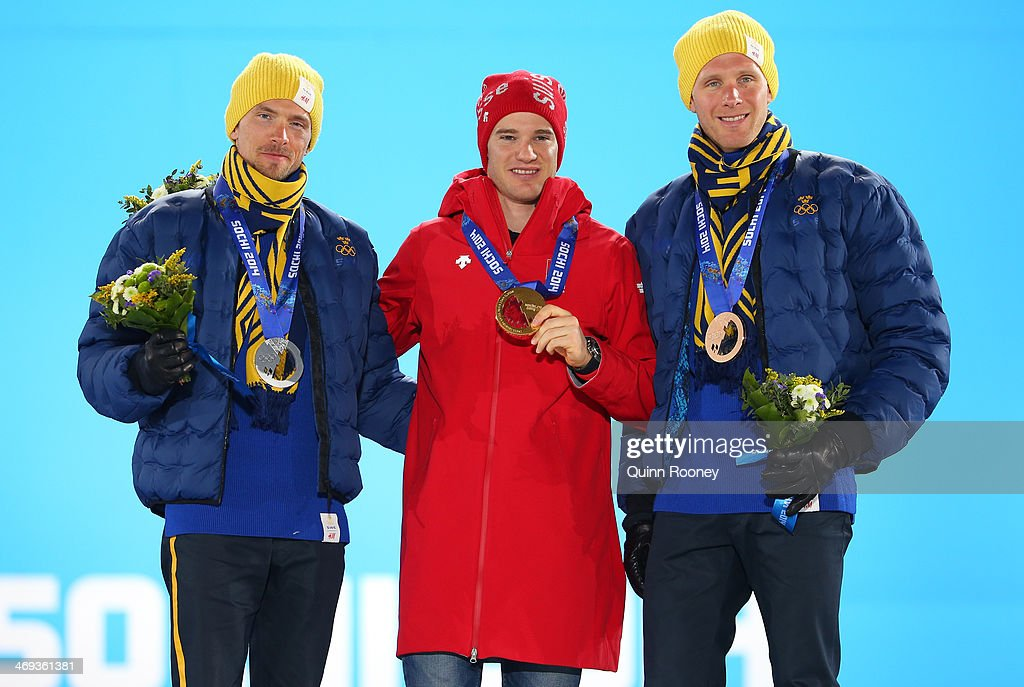 Silver medalist <a gi-track='captionPersonalityLinkClicked' href=/galleries/search?phrase=Johan+Olsson&family=editorial&specificpeople=724246 ng-click='$event.stopPropagation()'>Johan Olsson</a> of Sweden, gold medalist <a gi-track='captionPersonalityLinkClicked' href=/galleries/search?phrase=Dario+Cologna&family=editorial&specificpeople=4779620 ng-click='$event.stopPropagation()'>Dario Cologna</a> of Switzerland and bronze medalist Daniel Richardsson of Sweden celebrate on the podium during the medal ceremony for the Cross Country Men's 15km Classic event on day 7 of the Sochi 2014 Winter Olympics at Medals Plaza on February 14, 2014 in Sochi, Russia.