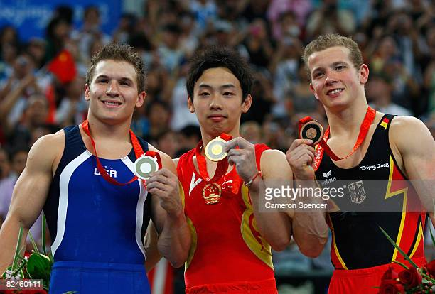Silver medalist Jonathan Horton of the USA gold medalist Zou Kai of China and bronze medalist Fabian Hambuchen of Germany pose on the podium during...