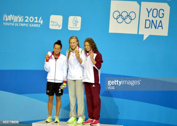 Silver medalist Julia Willers of Germany Gold medalist Ruta Meilutyte of Lithuania and Bronze medalist Anna Sztankovics of Hungary celebrate on the...