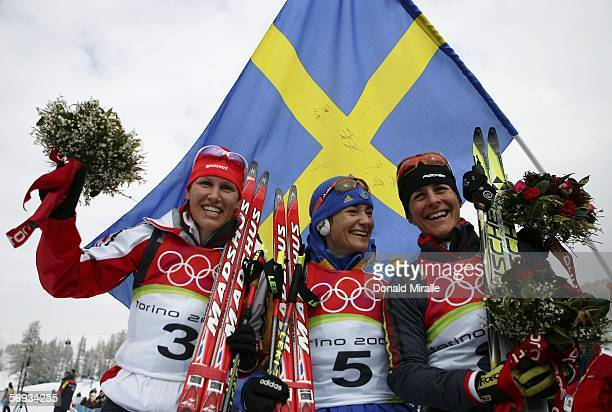 Silver medalist Kati Wilhelm of Germany gold medalist Anna Carin Olofsson of Sweden and bronze medalist Uschi Disl of Germany celebrate on the podium...