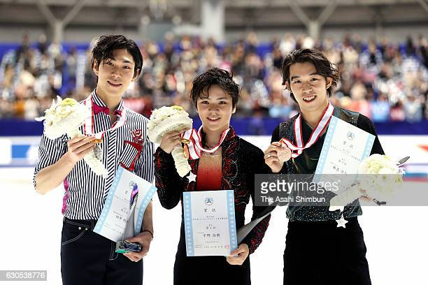 Silver medalist Keiji Tanaka gold medalist Shoma Uno and bronze medalist Takahito Mura pose on the podium at the medal ceremony for the Men's Singles...