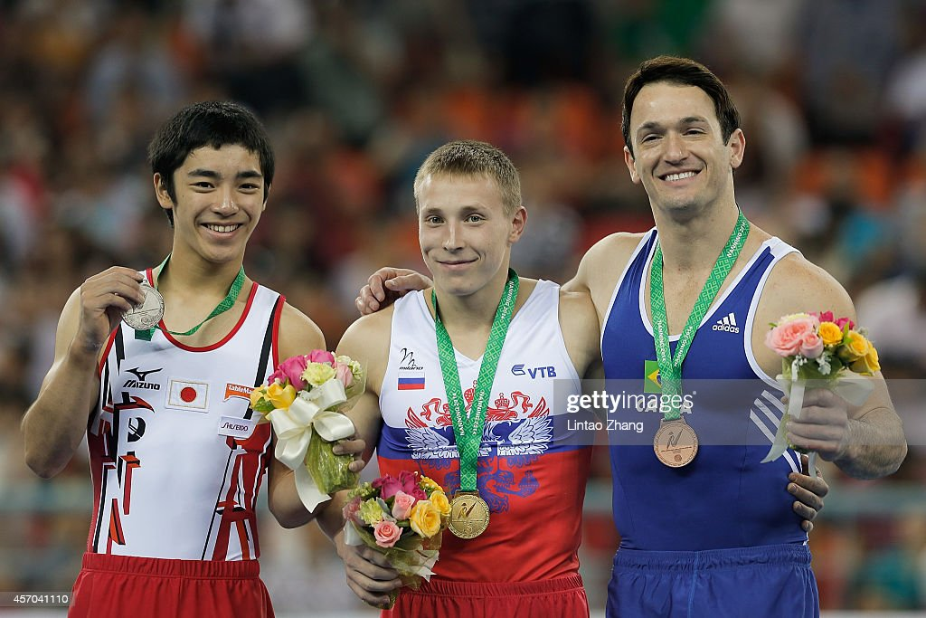 Silver medalist Kenzo Shirai of Japan gold medalist Denis Abliazin of Russia and bronze medalist Diego Hypolito of Brazil celebrate during the medal...