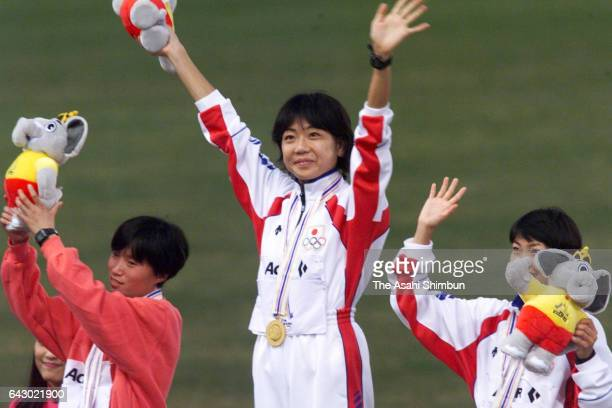 Silver medalist Kim ChangOk of North Korea gold medalist Naoko Takahashi of Japan and bronze medalist Tomoko Kai of Japan celebrate on the podium at...