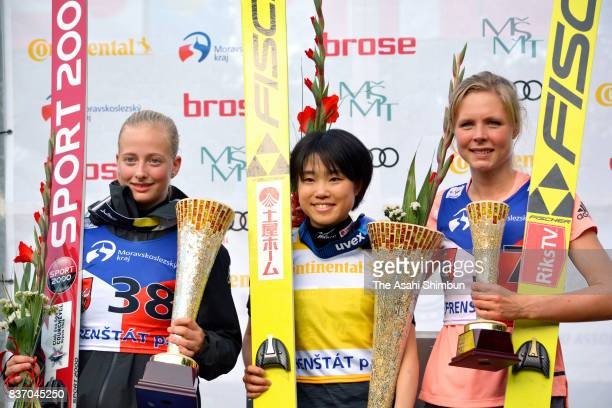 Silver medalist Lucile Morat of France gold medalist Yuki Ito of Japan and bronze medalist Maren Lundby of Norway celebrate on the podium during day...