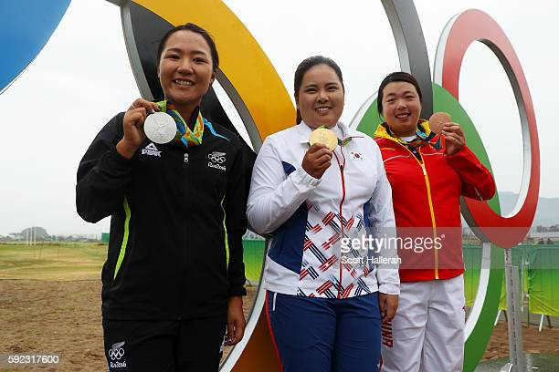 Silver medalist Lydia Ko of New Zealand gold medalist Inbee Park of Korea and bronze medalist Shanshan Feng of China pose by the olympic rings after...
