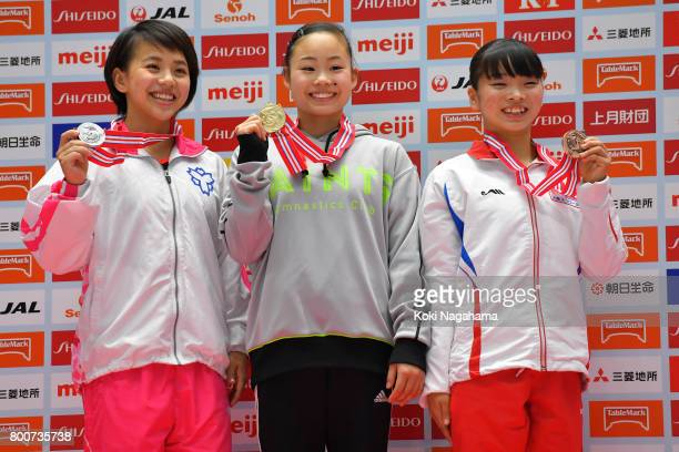 Silver medalist Mai Murakami Gold medalist Sae Miyakawa and Bronz medalist Mana Oguchi pose for photographs on the podium in the award ceremony for...