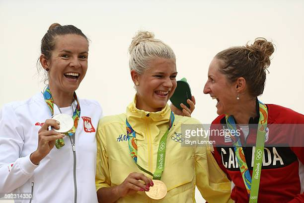 R] Silver medalist Maja Wloszczowska of Poland gold medalist Jenny Rissveds of Sweden and bronze medalist Catharine Pendrel of Canda celebrate on the...