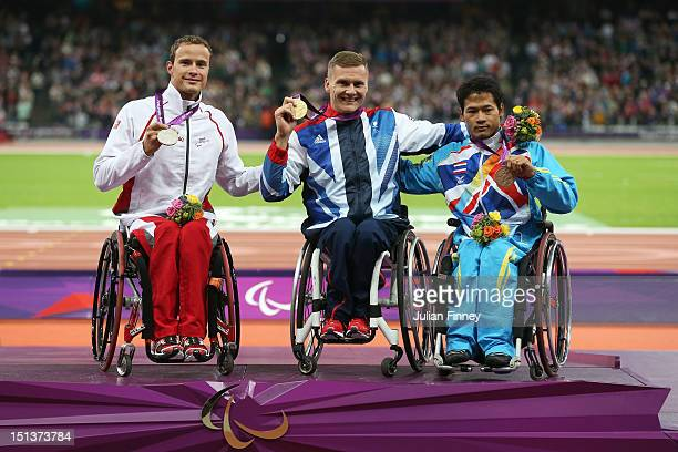 Silver medalist Marcel Hug of Switzerland Gold medalist David Weir of Great Britain and bronze medalist Saichon Konjen of Thailand pose on the during...