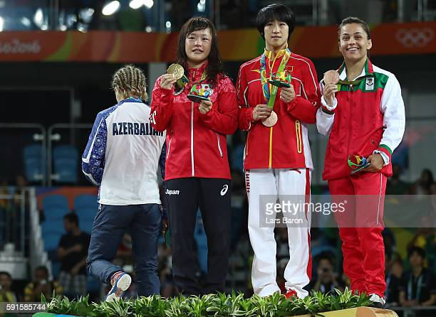 Silver medalist Mariya Stadnik of Azerbaijan walks off the podium as gold medalist Eri Tosaka of Japan bronze medalist Yanan Sun of China and bronze...