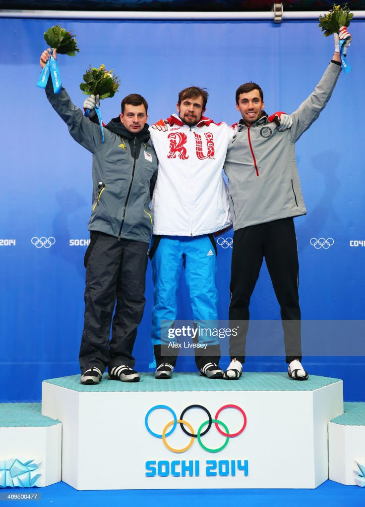 Silver medalist Martins Dukurs of Latvia, gold medalist Alexander Tretiakov of Russia and bronze medalist Matthew Antoine of the United States pose on the podium during the flower ceremony for the Men's Skeleton on Day 8 of the Sochi 2014 Winter Olympics at Sliding Center Sanki on February 15, 2014 in Sochi, Russia.