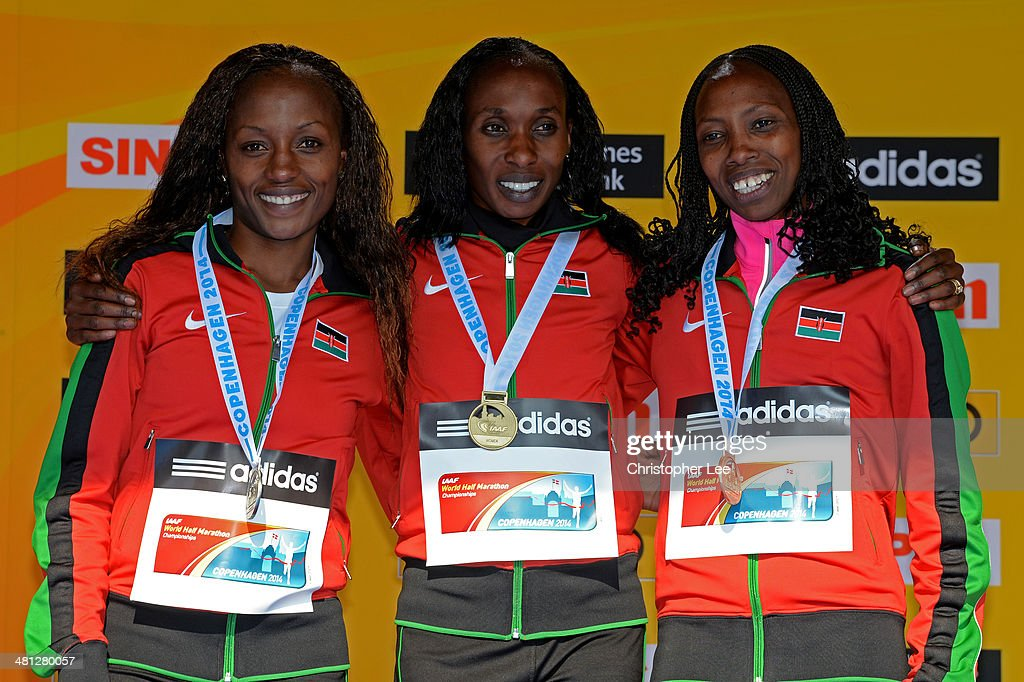 Silver medalist Mary Wacera Ngugi, Gold medalist Gladys Cherono and bronze medalist Selly Chepyego Kaptich of Kenya celebrate on the podium after the IAAF/Al-Bank World Half Marathon Championships on March 29, 2014 in Copenhagen, Denmark.