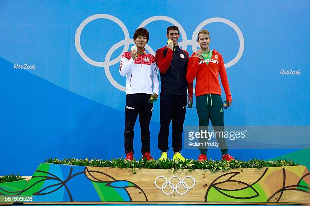 Silver medalist Masato Sakai of Japan gold medalist Michael Phelps of the United States and bronze medalist Tamas Kenderesi of Hungary pose on the...