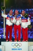 Silver medalist Maxim Vylegzhanin of Russia gold medalist Alexander Legkov of Russia and bronze medalist Ilia Chernousov of Russia celebrate in the...