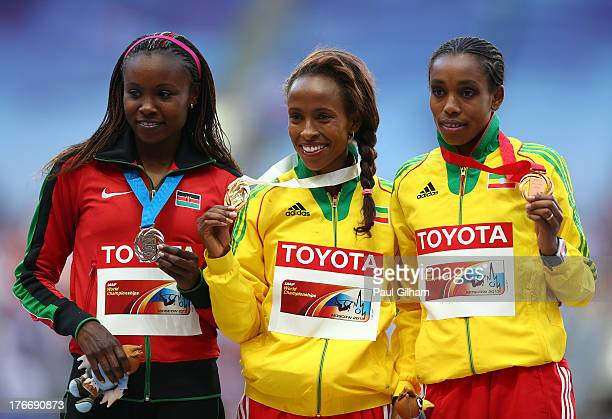 Silver medalist Mercy Cherono of Kenya gold medalist Meseret Defar of Ethiopia and bronze medalist Almaz Ayana of Ethiopia stand on the podium during...