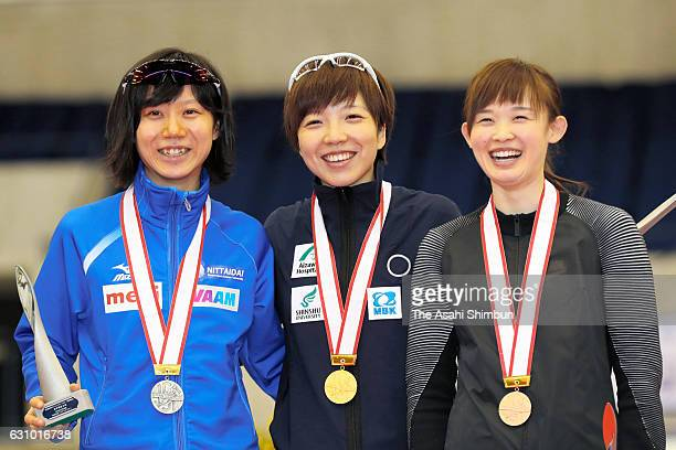 Silver medalist Miho Takagi gold medalist Nao Kodaira and bronze medalist Arisa Go celebrate on the podium at the medal ceremony for Women's Overall...