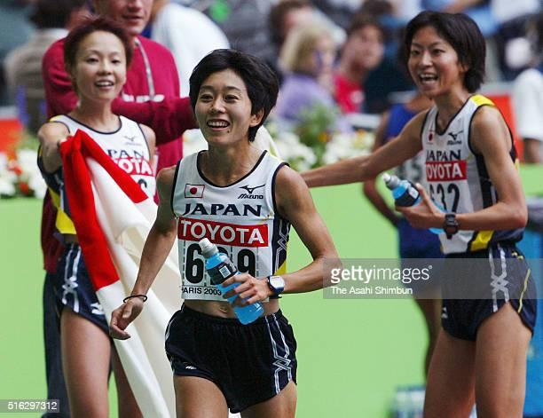Silver medalist Mizuki Noguchi bronze medalist Masako Chiba and fourth place Naoko Sakamoto of Japan celebrate after the Women's marathon during day...