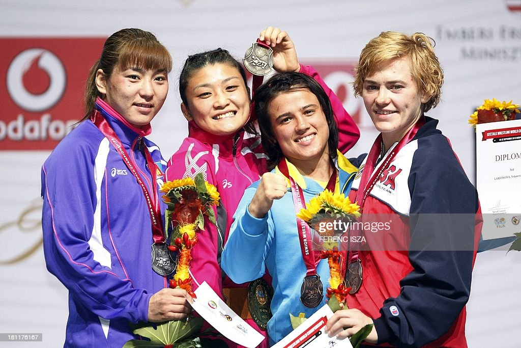 Silver medalist Mongolia's Munkhtuya Tungalag (L), gold medalist Japan's Kaori Icho (2ndL), bronze medalist Kazahstania's Yekaterina Larionova (2ndR) and bronze medalist USA's Elena Pirozhkova (R) celebrate on the podium of the women's free style 63 kg category of the World Wrestling Championships in Budapest on September 19, 2013. AFP PHOTO / FERENC ISZA