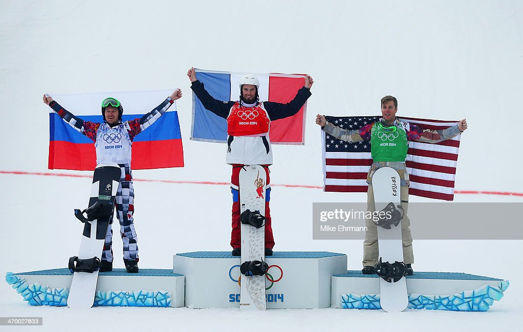 Silver medalist Nikolay Olyunin of Russia, gold medalist <a gi-track='captionPersonalityLinkClicked' href=/galleries/search?phrase=Pierre+Vaultier&family=editorial&specificpeople=818082 ng-click='$event.stopPropagation()'>Pierre Vaultier</a> of France and bronze medalist <a gi-track='captionPersonalityLinkClicked' href=/galleries/search?phrase=Alex+Deibold&family=editorial&specificpeople=2293880 ng-click='$event.stopPropagation()'>Alex Deibold</a> of the United States on the podium during the flower ceremony for the Men's Snowboard Cross Final on day eleven of the 2014 Winter Olympics at Rosa Khutor Extreme Park on February 18, 2014 in Sochi, Russia.