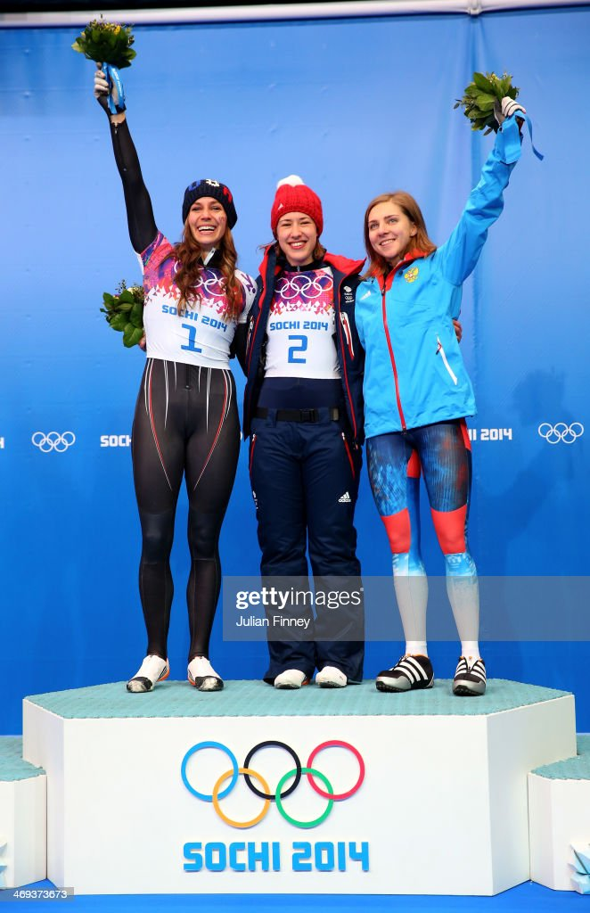 Silver medalist Noelle Pikus-Pace of the United States, gold medalist Lizzy Yarnold of Great Britain and bronze medalist Elena Nikitina of Russia celebrate on the podium during the flower ceremony for the Women's Skelton on Day 7 of the Sochi 2014 Winter Olympics at Sliding Center Sanki on February 14, 2014 in Sochi, Russia.