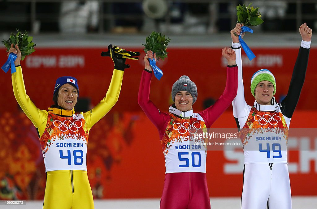 Silver medalist Noriaki Kasai of Japan, gold medalist Kamil Stoch of Poland and bronze medalist Peter Prevc of Slovenia celebrate on the podium during the flower ceremony after the Men's Large Hill Individual Final Round on day 8 of the Sochi 2014 Winter Olympics at the RusSki Gorki Ski Jumping Center on February 15, 2014 in Sochi, Russia.