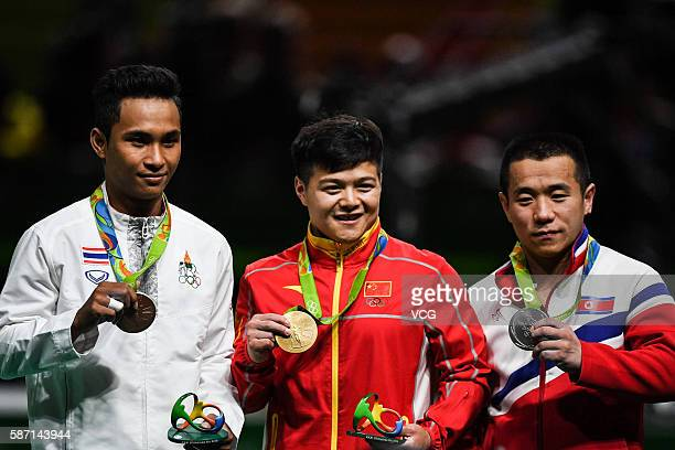 Silver medalist Om Yun Chol of North Korea gold medalist Long Qingquan of China and bronze medalist Sinphet Kruaithong of Thailand pose on the podium...