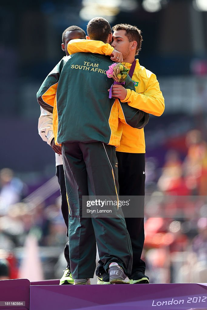 Silver medalist Oscar Pistorius of South Africa hugs gold medalist Alan Fonteles Cardoso Oliveira on the podium during the medal ceremony for the...