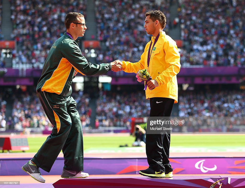 Silver medalist Oscar Pistorius of South Africa shakes hands with the gold medalist Alan Fonteles Cardoso Oliveira on the podium during the medal...