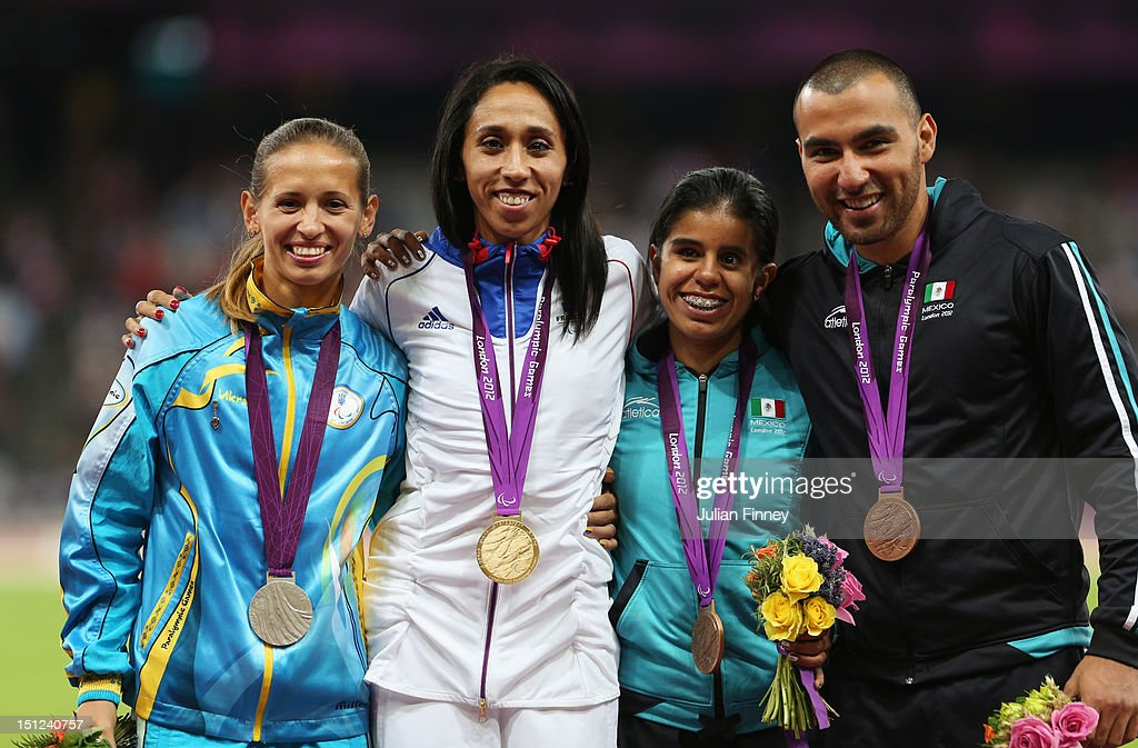 Silver medalist Oxana Boturchuk of Ukraine, Gold medalist <a gi-track='captionPersonalityLinkClicked' href=/galleries/search?phrase=Assia+El+Hannouni&family=editorial&specificpeople=2905697 ng-click='$event.stopPropagation()'>Assia El Hannouni</a> of France and bronze medalist Daniela Eugenia Velasco Maldonado of Mexico and her guide Jose Guadalupe Fuentes Ortiz pose on the podium during the medal ceremony for the Women's 400m - T12 on day 6 of the London 2012 Paralympic Games at Olympic Stadium on September 4, 2012 in London, England.