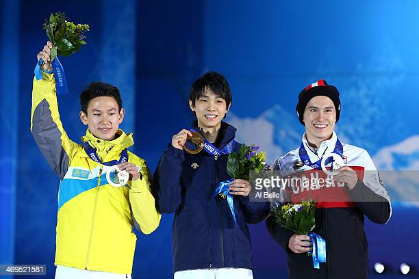 Silver medalist Patrick Chan of Canada gold medalist Yuzuru Hanyu of Japan and bronze medalist Denis Ten of Kazakhstan on the podium during the medal...