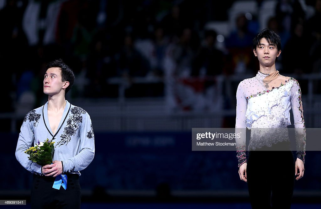 Silver medalist Patrick Chan of Canada stands next to Yuzuru Hanyu of Japan who won the gold after the Figure Skating Men's Free Skating on day seven of the Sochi 2014 Winter Olympics at Iceberg Skating Palace on February 14, 2014 in Sochi, Russia.