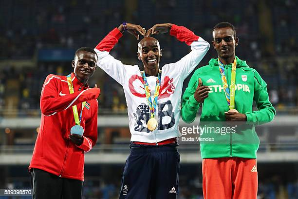 Silver medalist Paul Kipngetich Tanui of Kenya Gold medalist Mohamed Farah of Great Britain and Bronze medalist Tamirat Tola of Ethiopia celebrate on...
