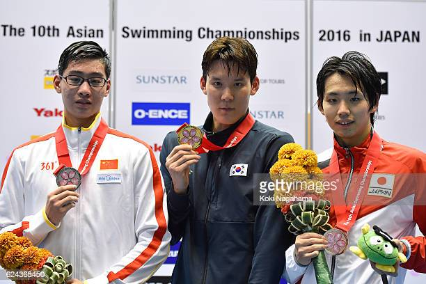 Silver medalist Qiu Ziao of China and Gold medalist Park Taehwan of South Korea and Bronze medalist Shogo Takeda of Japan pose for photographs on the...