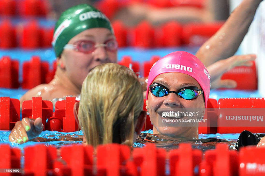 Silver medalist Russia's Yuliya Efimova (R) celebrates with bronze medalist US swimmer Jessica Hardy (C) next to Gold medalist Lithuania's Ruta Meilutyte at the end of the final of the women's 100-metre breaststroke swimming event in the FINA World Championships at Palau Sant Jordi in Barcelona on July 30, 2013.