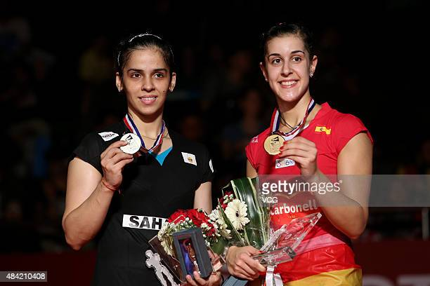 Silver medalist Saina Nehwal of India and gold medalist Carolina Marin of Spain celebrate on the podium after the Women's Singles final match of the...
