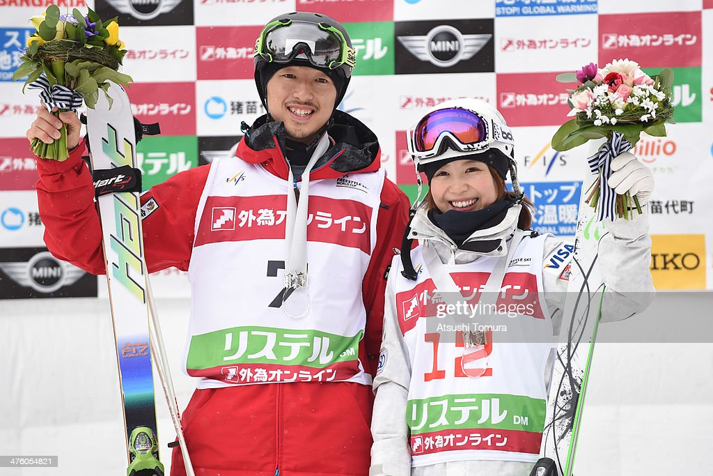 Silver medalist Sho Endo of Japan and bronze medalist Junko Hoshino of Japan pose on the podium after the medal ceremony for dual moguls during 2014...