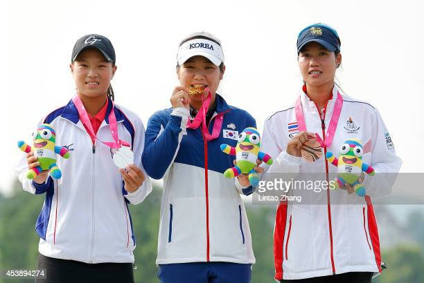 Silver medalist SsuChia Cheng of Chinese Taipei Gold medalist Soyoung Lee of Korea and Bronze medalist Supamas Sangchan of Thailand celebrate during...