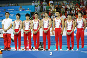 Silver medalist team of Japan celebrates during the medal ceremony after the Men's Team Final of the 45th Artistic Gymnastics World Championships at...