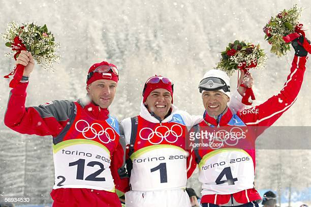 Silver medalist Tomasz Sikora of Poland gold medalist Michael Greis of Germany and bronze medalist Ole Einar Bjoerndalen of Norway celebrate on the...