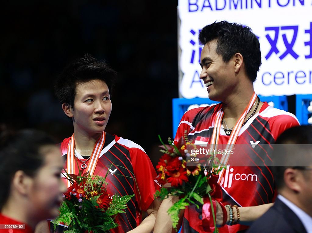 Silver medalist Tontowi Ahmad (R) of India talks to his partner Liliyana Natsir of India during the award ceremony of the mixed doubles at the 2016 Badminton Asia Championships in Wuhan, central China's Hubei province on May 1, 2016. / AFP / STR / China OUT