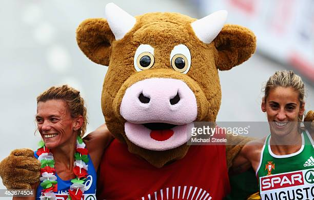Silver medalist Valerio Straneo of Italy mascot 'Cooly' and bronze medalist Jessica Augusto of Portugal celebrate after the Women's Marathon final...