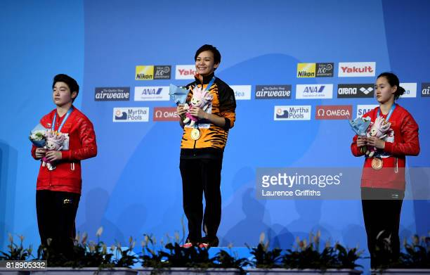 Silver medalist Yajie Si of China gold medalist Jun Hoong Cheong of Malaysia and bronze medalist Qian Ren of China pose with the medals won during...