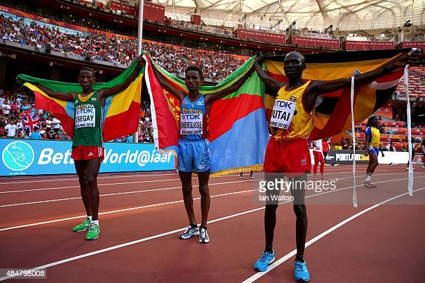 Silver medalist Yemane Tsegay of Ethiopia gold medalist Ghirmay Ghebreslassie of Eritrea and bronze medalist Munyo Solomon Mutai of Uganda celebrate...