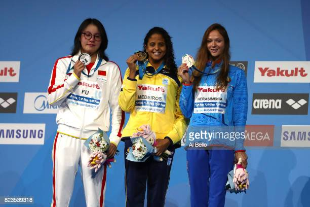 Silver medalist Yuanhui Fu of China and gold medalist Etiene Medeiros of Brazil and bronze medalist Aliaksandra Herasimenia of Belarus pose with the...