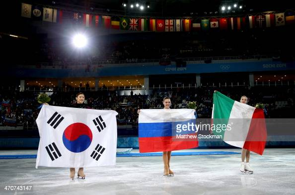 Silver medalist Yuna Kim of South Korea gold medalist Adelina Sotnikova of Russia and bronze medalist Carolina Kostner of Italy celebrate during the...