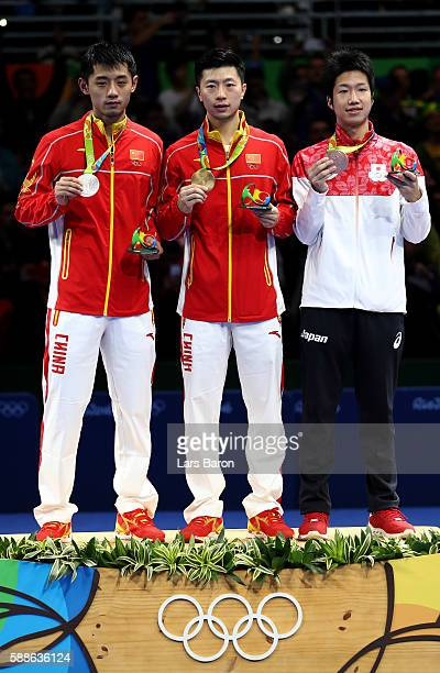 Silver medalist Zhang Jike of China gold medalist Ma Long of China and bronze medalist Jun Mizutani of Japan pose on the podium during the medal...