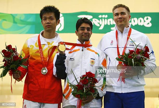 Silver medalist Zhu Qinan of China Gold medalist Abhinav Bindra of India and Bronze medalist Henri Hakkinen of Finland pose after the Men's 10m Air...