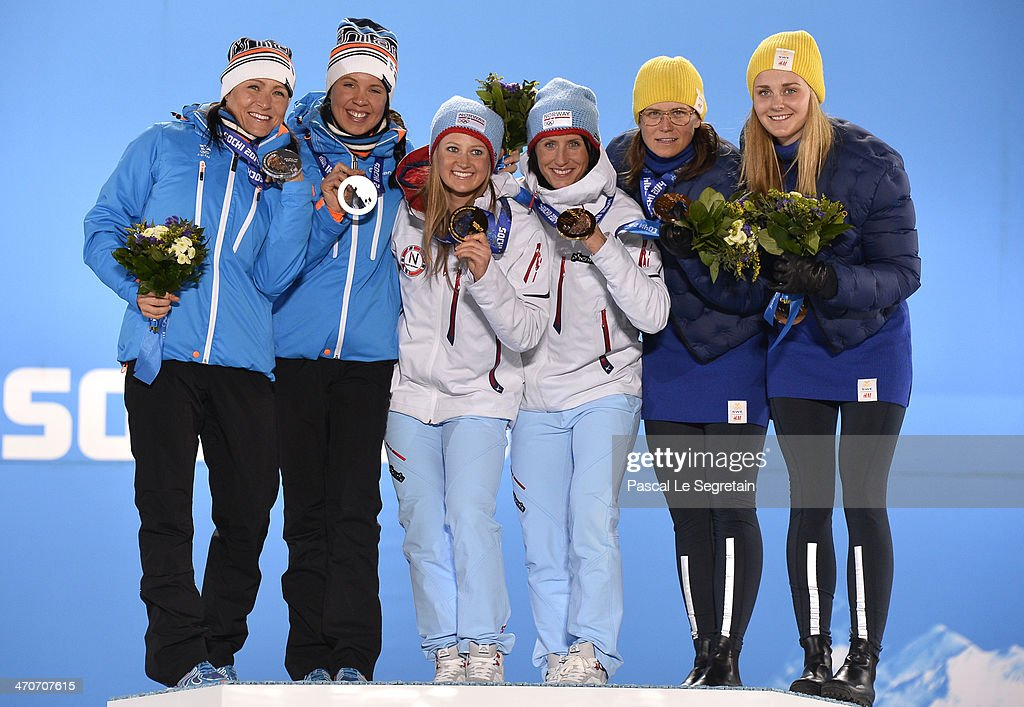 Silver medalists <a gi-track='captionPersonalityLinkClicked' href=/galleries/search?phrase=Aino-Kaisa+Saarinen&family=editorial&specificpeople=769322 ng-click='$event.stopPropagation()'>Aino-Kaisa Saarinen</a> and <a gi-track='captionPersonalityLinkClicked' href=/galleries/search?phrase=Kerttu+Niskanen&family=editorial&specificpeople=7526325 ng-click='$event.stopPropagation()'>Kerttu Niskanen</a> of Finland, gold medalists <a gi-track='captionPersonalityLinkClicked' href=/galleries/search?phrase=Ingvild+Flugstad+Oestberg&family=editorial&specificpeople=7427144 ng-click='$event.stopPropagation()'>Ingvild Flugstad Oestberg</a> and <a gi-track='captionPersonalityLinkClicked' href=/galleries/search?phrase=Marit+Bjoergen&family=editorial&specificpeople=216406 ng-click='$event.stopPropagation()'>Marit Bjoergen</a> of Norway and bronze medalists <a gi-track='captionPersonalityLinkClicked' href=/galleries/search?phrase=Ida+Ingemarsdotter&family=editorial&specificpeople=5640296 ng-click='$event.stopPropagation()'>Ida Ingemarsdotter</a> and <a gi-track='captionPersonalityLinkClicked' href=/galleries/search?phrase=Stina+Nilsson&family=editorial&specificpeople=10116472 ng-click='$event.stopPropagation()'>Stina Nilsson</a> of Sweden celebrate on the podium during the medal ceremony for the Cross Country Ladies' Team Sprint on day thirteen of the Sochi 2014 Winter Olympics at at Medals Plaza on February 20, 2014 in Sochi, Russia.